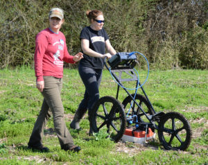TVA archaeologist Erin Pritchard and Sarah Lowery from New South Associates use a ground-penetrating radar machine during the geophysical survey of the site. Credit: TVA