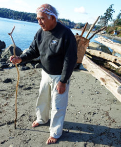 Ed Carriere models how the tumpline he made would work to carry wood and other items in a replica Biderbost pack basket that he wove. He is on his beach in front of the home on his Indian Allotment lands where he was born and has lived most of his life. Credit: Dale Croes