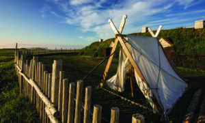 This picture shows historically-accurate reconstructions of a Norse tent and, behind it, a sod and timber longhouse. The walls of the longhouse are six-feet thick. Credit: Parks Canada
